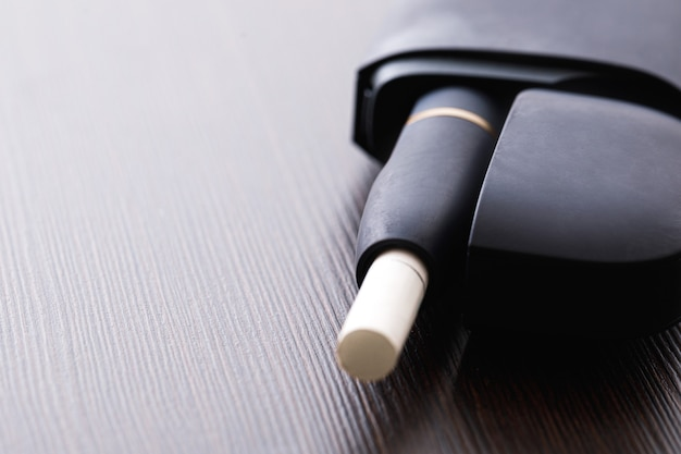 Sistema di riscaldamento del tabacco sul tavolo di legno. alternativa alle sigarette tradizionali