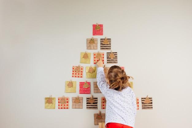 Bambino di 3 anni ragazza in piedi indietro che mostra al calendario dell'avvento fatto a mano di natale a forma di albero di natale sul muro nella stanza dei bambini.