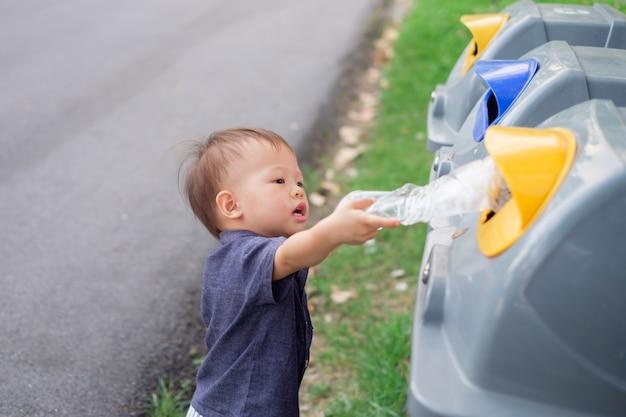 Bambino neonato bambino gettare la bottiglia di plastica nel cestino della spazzatura al parco pubblico