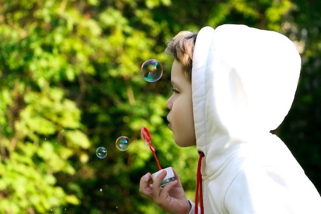 Bambino che soffia bolle di sapone. cammina durante la quarantena. bolle colorate, sogna l'estate.