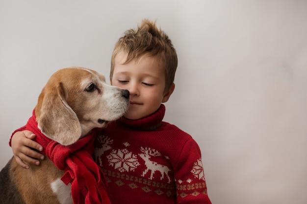 Ragazzo del bambino in giacca di natale che tiene beagle in sciarpa rossa