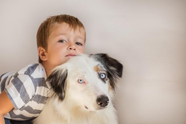 Ragazzo del bambino che tiene pastore australiano indoor. migliori amici consept.