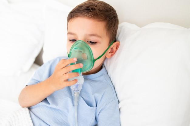 Il bambino giace a letto malato con una maschera per inalazione