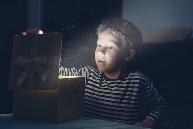 Ragazzo del bambino che apre una scatola regalo di natale dorata con polvere magica e luce proveniente dall'immagine presente, dai toni retrò.