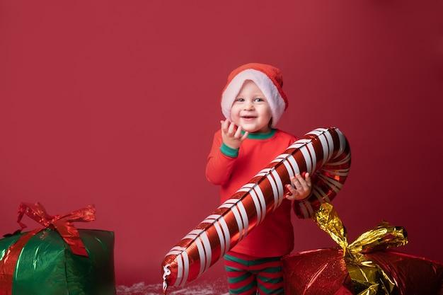 Ragazzo del bambino in cappello della santa con i regali di natale e il bastoncino di zucchero su uno sfondo rosso.