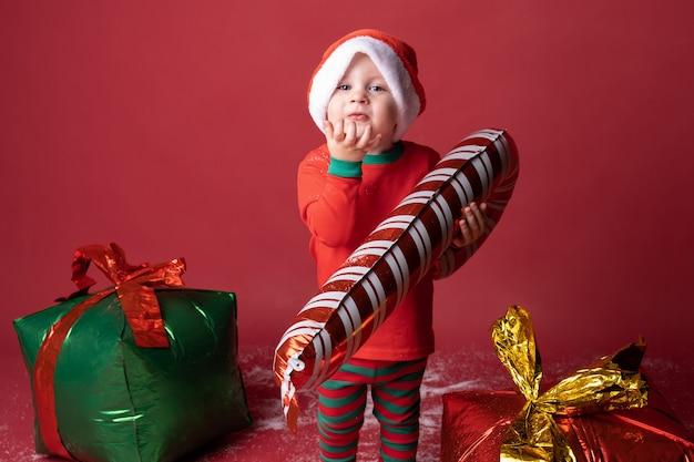 Ragazzo del bambino in cappello della santa con i regali di natale e il bastoncino di zucchero sul rosso