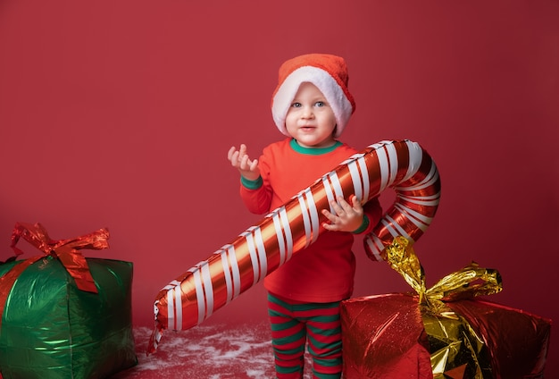 Ragazzo del bambino in cappello della santa con i regali di natale e il bastoncino di zucchero
