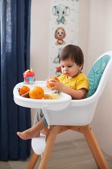 Il bambino con i capelli scuri in una maglietta gialla si siede su un seggiolone e mangia frutta.