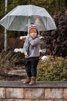 Ragazzo del bambino con l'ombrello nella sosta di autunno.