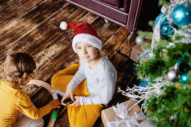 Ragazzi del bambino che costruiscono ferrovia e giocano con il trenino sotto l'albero di natale. bambini con regali di natale. periodo natalizio.