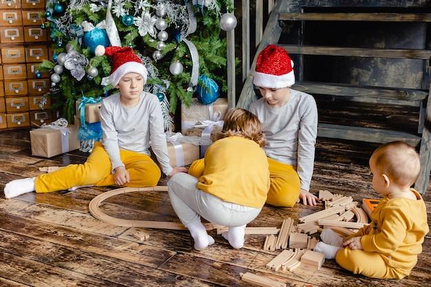 Ragazzi del bambino con la ferrovia della costruzione del cappello della santa e che giocano con il trenino sotto l'albero di natale. bambini con regali di natale. periodo natalizio.