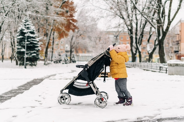 Bambino del bambino che spinge il passeggino con il fratello dentro. giornata invernale nevosa. periodo natalizio