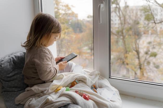 Bambino bambino utilizzando il telefono a casa, scattare foto e giocare