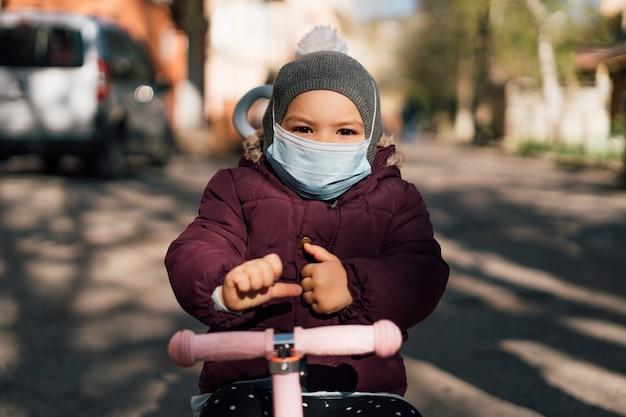 Bambino del bambino che indossa maschera medica viso all'aperto nella stagione fredda