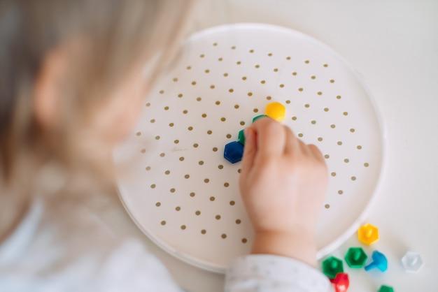 Il bambino crea una figura da un mosaico di plastica.