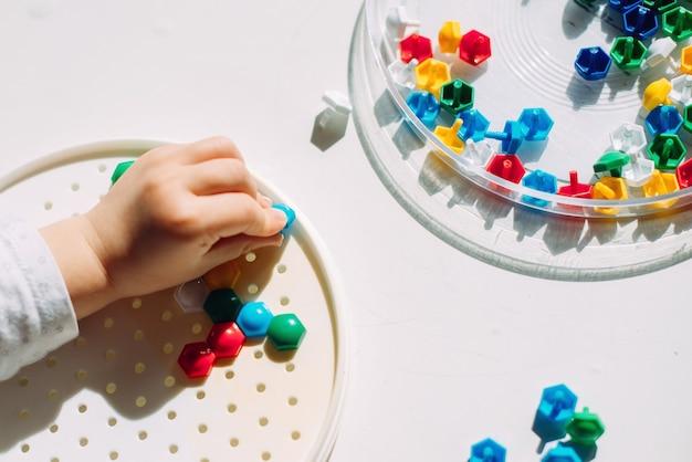 Il bambino crea una figura a mosaico multicolore.