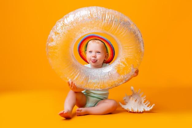 La ragazza del bambino in tuta blu e cerchio di nuoto si siede su una parete gialla