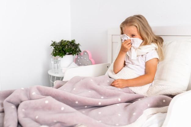 La ragazza del bambino è sdraiata a letto. il bambino ha freddo e malato e ha il naso che cola e il moccio.