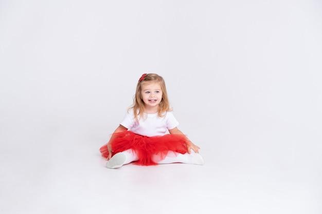 Ragazza del bambino in gonna rossa e maglietta bianca su sfondo bianco. concetto di san valentino.