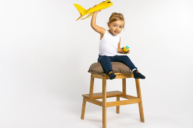 Ragazza del bambino che si siede e posa con uno stereotipo di genere del giocattolo dell'aereo giallo