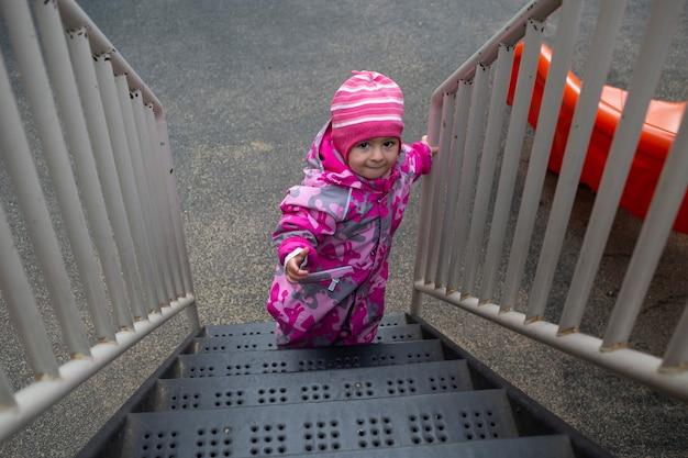 Ragazza del bambino in cappotto invernale salendo le scale del parco giochi all'aperto vista dall'alto