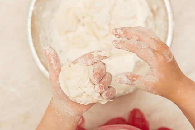 Le mani dei bambini impediscono la pasta per la torta