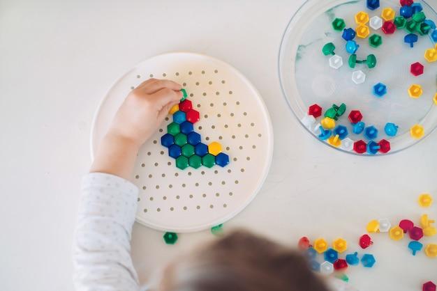 Bambino che gioca a mosaico sul tavolo a casa.
