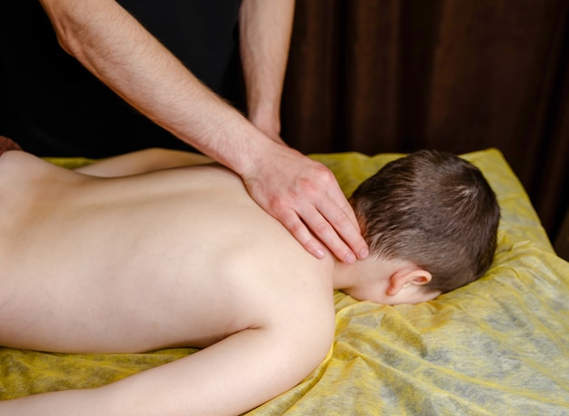 Il bambino si rilassa da un massaggio terapeutico. fisioterapista che lavora con il paziente in clinica sul retro di un bambino