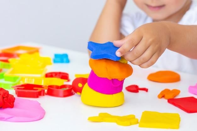 Il bambino scolpisce dalla plastilina colorata su un tavolo bianco