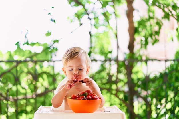 Il bambino con la faccia sporca si siede sul balcone e mangia la frutta