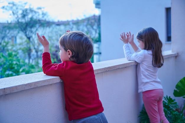 Bambini che applaudono dal balcone
