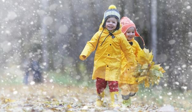 I più piccoli in una passeggiata nel parco autunnale. primo gelo e prima neve nel bosco autunnale. i bambini giocano nel parco con neve e foglie.