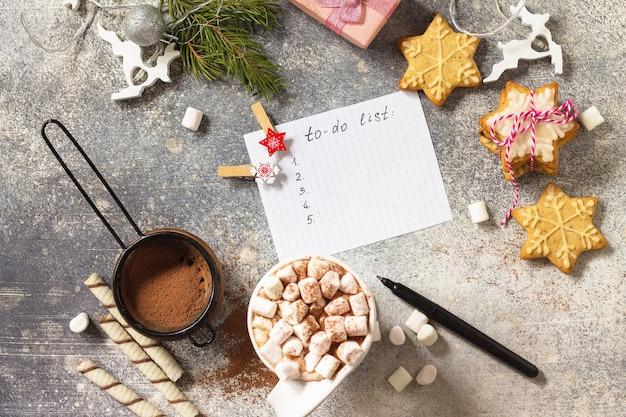 Lista delle cose da fare tazza di cioccolata calda con marshmallow dolci natalizi vista dall'alto piatta