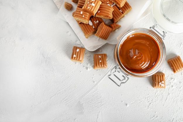 Caramelle toffee salate sul tagliere con caramello fuso in un barattolo di vetro nelle vicinanze su bianco