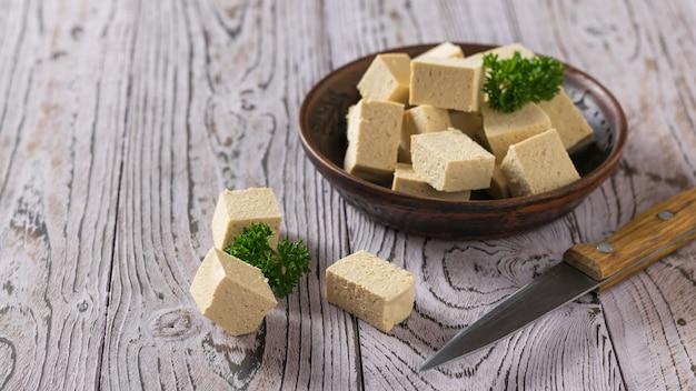 Formaggio di tofu in una ciotola di argilla e un coltello su una superficie di legno. formaggio di soia. prodotto vegetariano.
