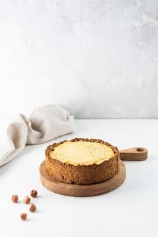 Cheesecake al tofu con caramello salato e noci su una tavola di legno