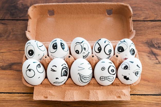 Insieme siamo più forti. vista dall'alto di uova divertenti con diverse emozioni che giacciono in un contenitore sulla scrivania di legno