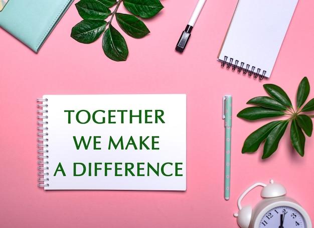 Insieme facciamo la differenza è scritto in verde su un blocco note bianco su una superficie rosa circondato da blocchi per appunti, penne, sveglia bianca e foglie verdi