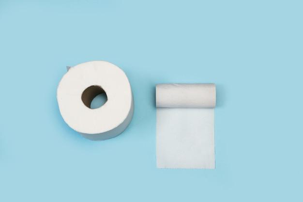 Un rotolo di carta igienica e altri quasi vuoti su fondo azzurro