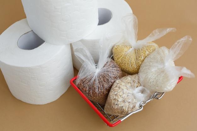 Carta igienica e cereali vari in sacchetti di plastica in un cestino della spesa su sfondo marrone