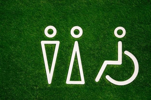 Segno di servizi igienici per uomini e donne con disabilità sull'erba verde