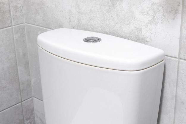 Cisterna del serbatoio della toilette della toilette in ceramica bianca nell'interno moderno del bagno con la piastrella in marmo