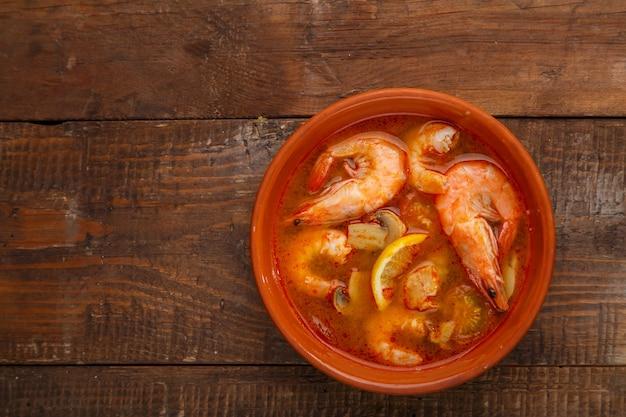 Zuppa di tom yam con gamberetti in un piatto su un tavolo di legno foto orizzontale