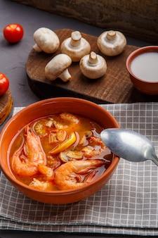 Zuppa di tom yam con gamberetti in una zuppiera su uno sfondo di cemento accanto a una ciotola con pomodori di latte di cocco e funghi su un supporto di legno. foto verticale