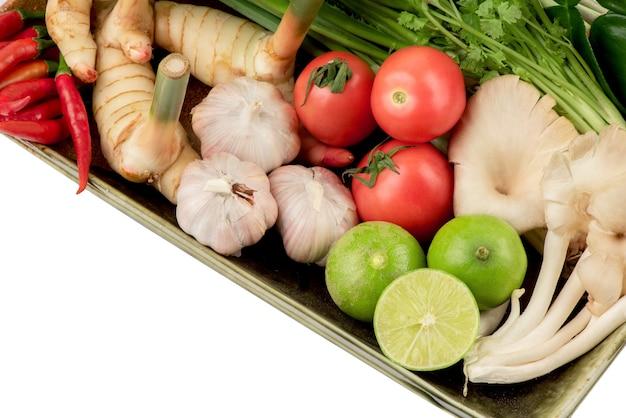 Tom yum contiene peperoncino, scalogno, citronella, foglie di lime kaffir, limone, galanga, coriandolo, cipolla e altro isolato su bianco.