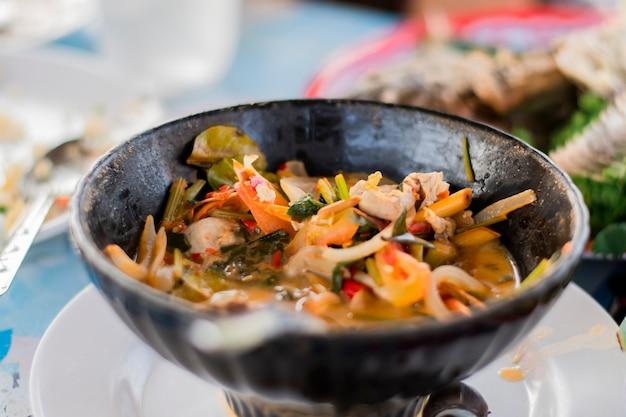 Zuppa tom yum in una ciotola nera sul tavolo da pranzo