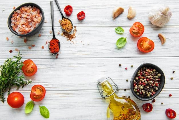 Pomodoro, basilico e pepe con aglio su legno bianco