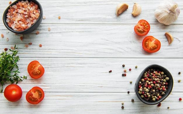 Pomodoro, basilico e pepe con aglio sulla tavola di legno bianca