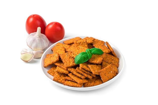 Cracker al pomodoro in un piatto bianco e ingredienti aglio e pomodori nel muro, isolato su una scrivania bianca.