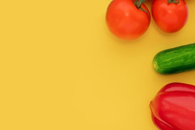 Pomodoro, cetriolo, pepe su uno sfondo giallo brillante, vista dall'alto, piatto, copia spazio. concetto di alimentazione sana, slim.